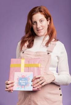 Mujer embarazada embarazada de ángulo bajo con regalo y tarjeta de felicitación