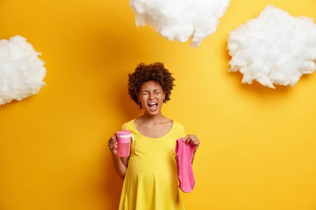 La mujer embarazada emocional que llora se siente cansada de comprar cosas necesarias para el bebé, se para con la boca abierta, sostiene un traje rosado y una botella de agua, expresa emociones negativas. concepto de embarazo