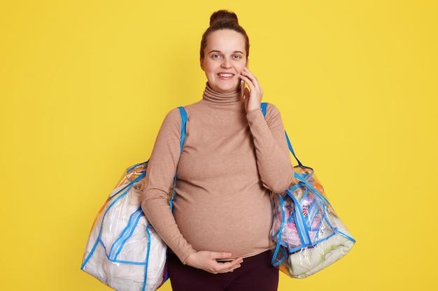 La mujer embarazada empaqueta las cosas del bebé de encaje. preparándose para el parto en casa. preparándose y empacando para el hospital, posando aislado sobre una pared amarilla y hablando por teléfono.