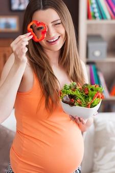 Mujer embarazada con ensalada saludable en casa
