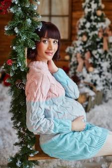 Mujer embarazada está esperando navidad cerca del árbol de navidad