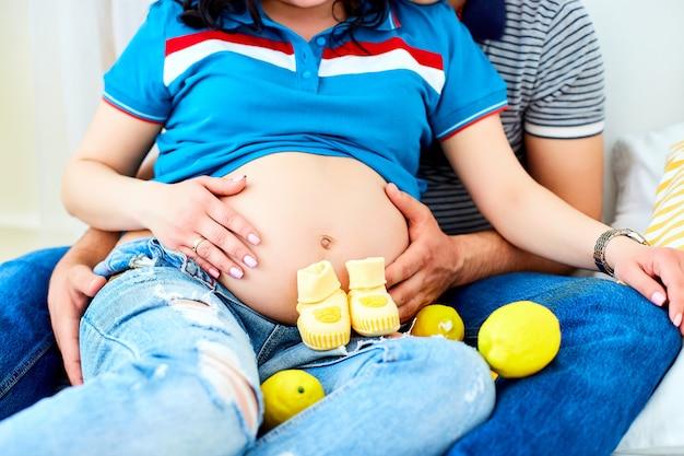 Mujer embarazada y esposo amoroso abrazando la barriga en casa.