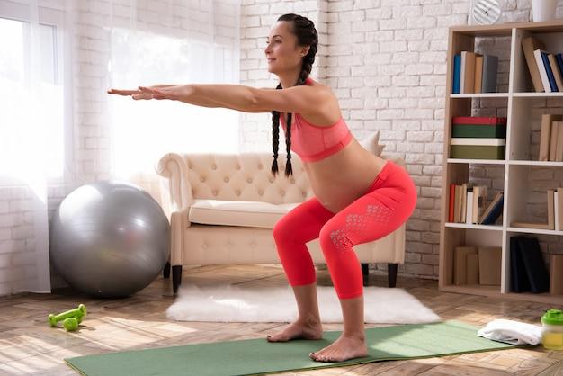 Mujer embarazada se estira y entrena vientre en casa
