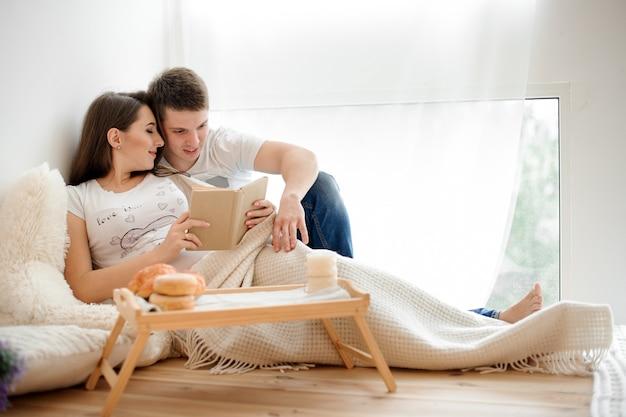 Mujer embarazada feliz que miente y que lee el libro en la cama con el marido