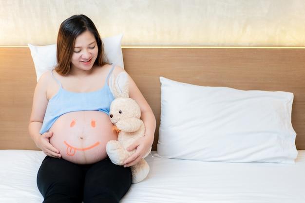 Mujer embarazada con gran barriga y una linda muñeca de conejito
