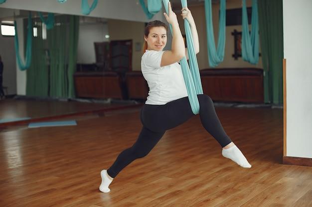 Mujer embarazada haciendo yoga en un gimnasio