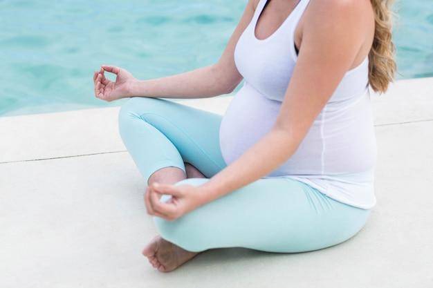 Mujer embarazada haciendo yoga junto a la piscina.
