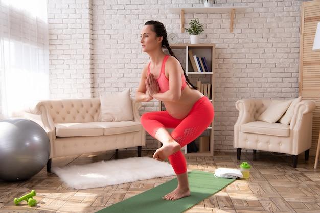 La mujer embarazada está haciendo yoga y medita en casa