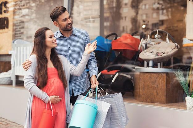 Una mujer embarazada con un hombre caminando por la ventana de la tienda.