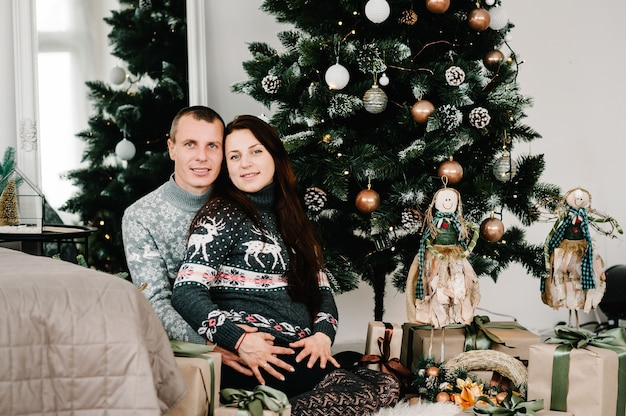 Mujer embarazada con hombre cerca del árbol de navidad en casa. ¡feliz navidad y felices fiestas! concepto de embarazo, vacaciones, personas y expectativa.