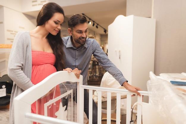 Una mujer embarazada y un hombre eligen una cuna.