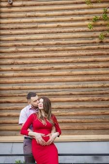 La mujer embarazada y el hombre de la familia feliz están de pie delante de la pared de madera