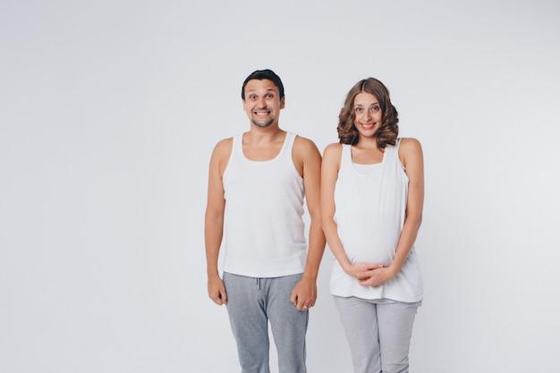 Mujer embarazada y hombre en ropa deportiva. la niña sostiene su estómago con la boca abierta y una sonrisa en su rostro.