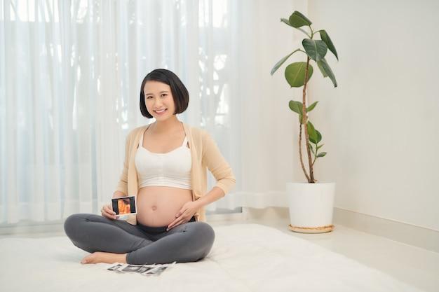 Mujer embarazada con imagen de ultrasonido cerca del vientre
