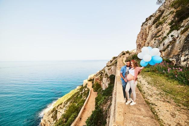 Mujer embarazada joven belleza saludable con su esposo y globos al aire libre