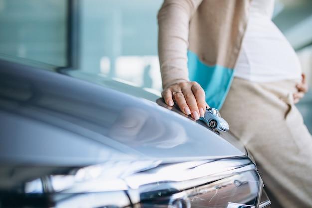 Mujer embarazada joven que elige un coche en una sala de exposición de automóviles