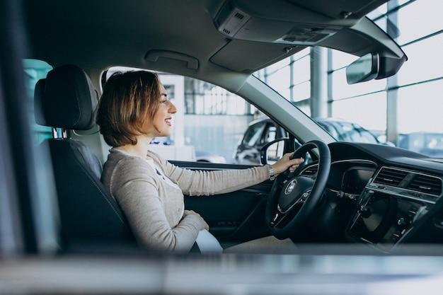 Mujer embarazada joven que prueba un coche en la sala de exposición de automóviles