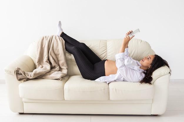 Mujer embarazada latina con tablet pc mientras está acostado en el sofá en casa. embarazo e información para el concepto de paternidad.
