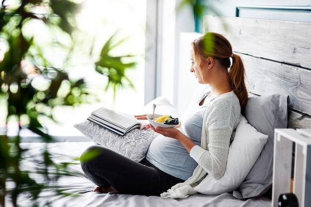 Mujer embarazada leyendo un libro en el dormitorio