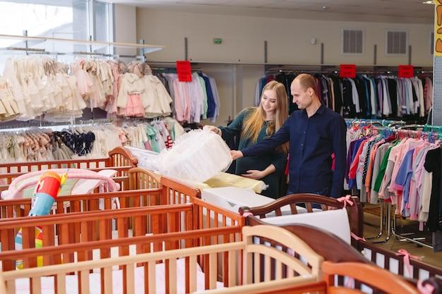 La mujer embarazada con el marido elige una cuna en la tienda.