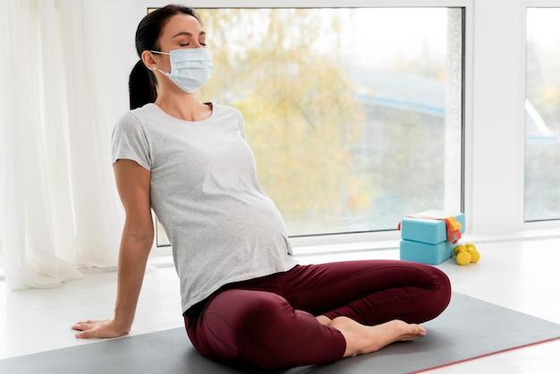 Mujer embarazada con máscara médica relajante