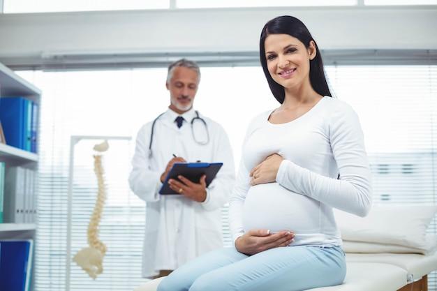 Mujer embarazada con médico en clínica