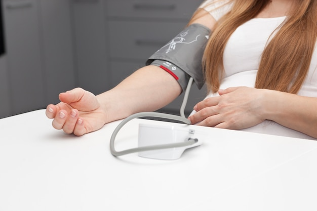 La mujer embarazada mide la presión arterial en casa.