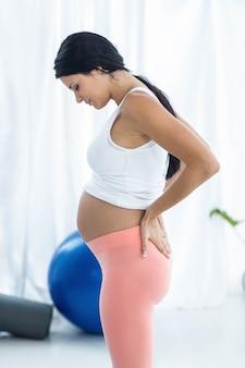 Mujer embarazada mirando hacia abajo mientras hace ejercicio en casa