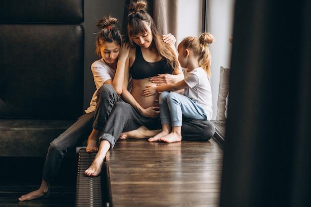 Mujer embarazada con niños sentados junto a la ventana