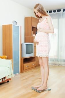 Mujer embarazada de pie en básculas de baño