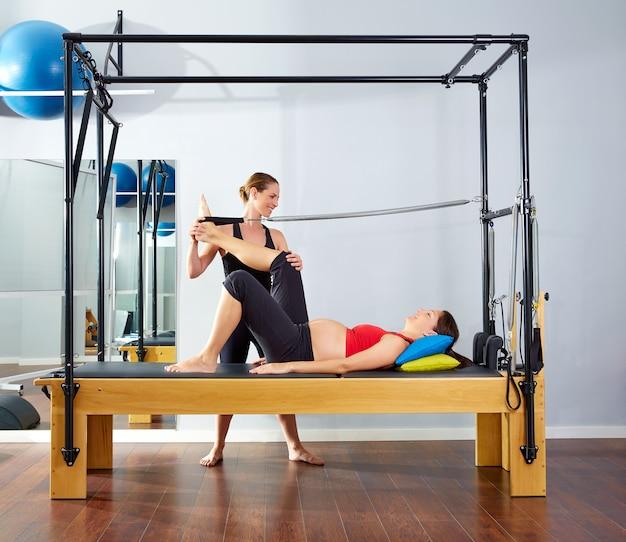 Mujer embarazada pilates reformer pierna primavera