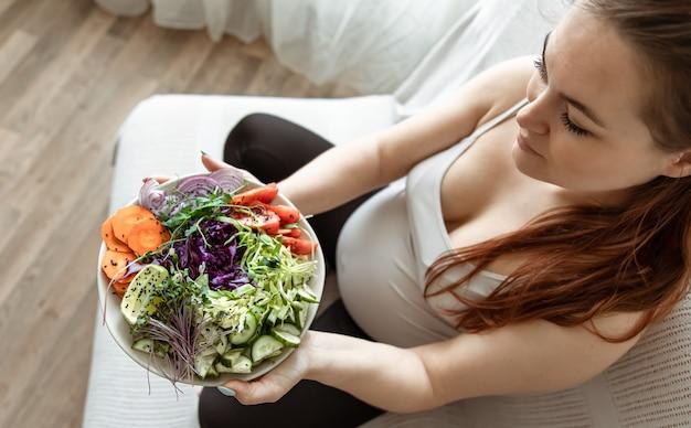 Mujer embarazada con un plato de ensalada de verduras frescas en casa en la vista superior del sofá.