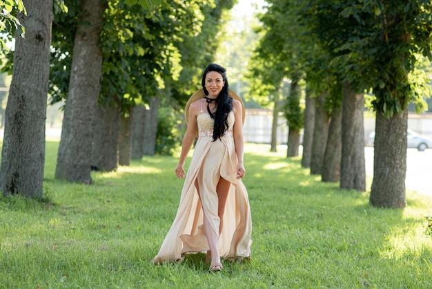 Mujer embarazada posando con un vestido beige sobre un fondo de árboles verdes.