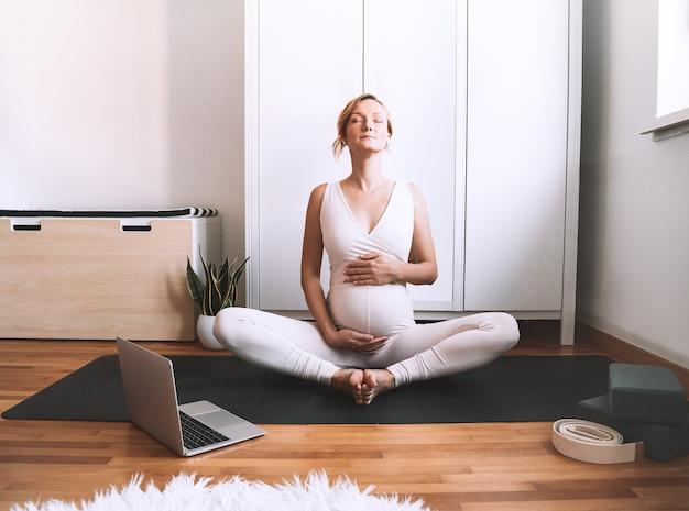 Mujer embarazada practicando yoga en casa con portátil ejercicio femenino meditar durante el embarazo