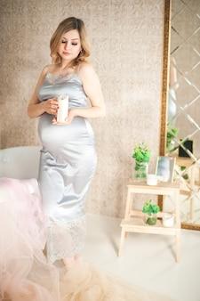 Mujer embarazada en el primer plano del baño. embarazada cerca del baño en un espacio gris de bata y copia.