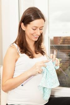 Mujer embarazada que hizo punto ropa de bebé.