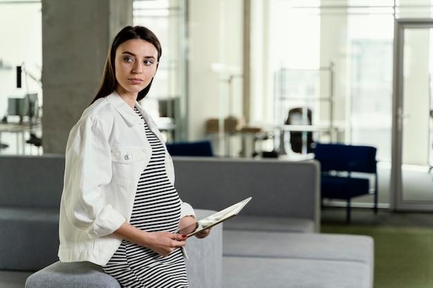 Mujer embarazada que trabaja en la oficina