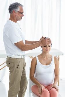 Mujer embarazada recibiendo un masaje en la cabeza de masajista en casa