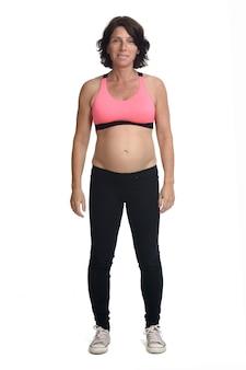 Mujer embarazada con ropa deportiva aislado sobre fondo blanco.