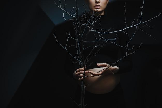 La mujer embarazada en ropa negra se coloca debajo de la pared gris y sostiene una ramificación de árbol