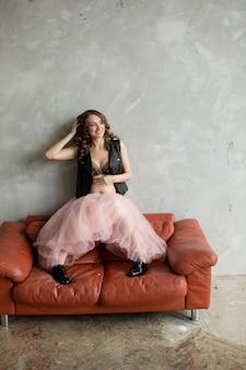 Mujer embarazada en rosa en el sofá