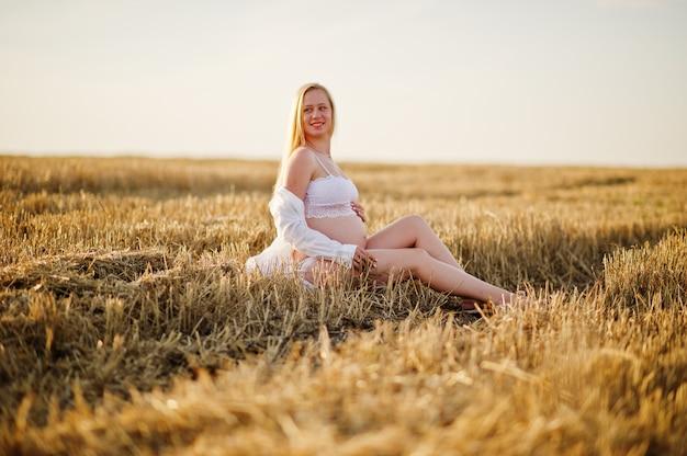 Mujer embarazada rubia en campo de corona en ropa interior blanca ropa puesta de sol