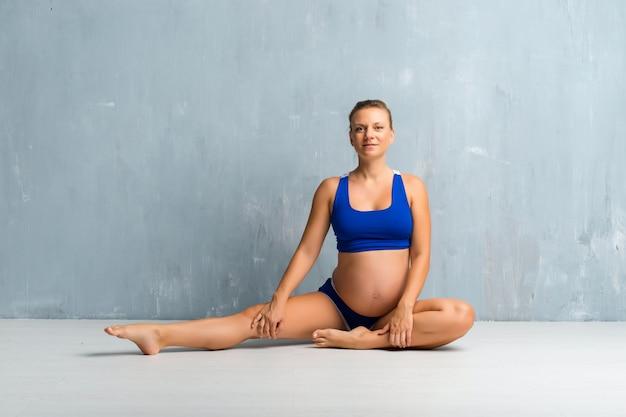 Mujer embarazada rubia haciendo deporte y estiramiento