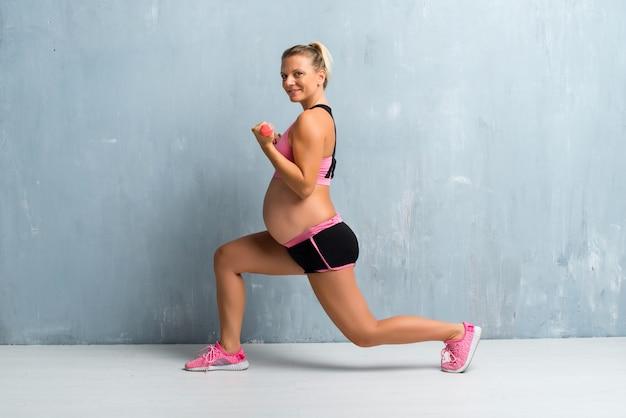 Mujer embarazada rubia haciendo deporte haciendo levantamiento de pesas