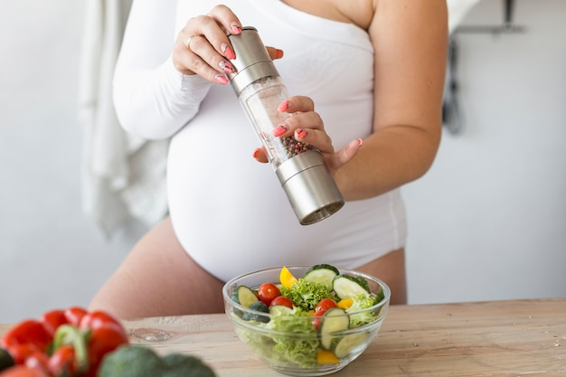 Mujer embarazada sazonar su ensalada