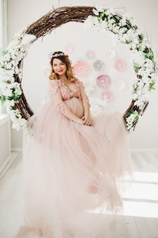 Mujer embarazada sentada en gran corona floral decorada