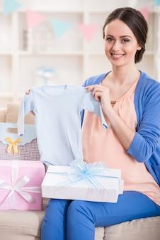 Mujer embarazada está sentada con regalos en un baby shower.