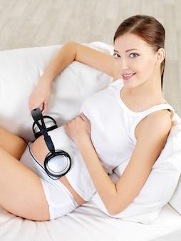 Mujer embarazada sentada en un sofá blanco en casa y escuchando música en auriculares