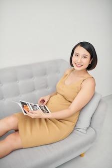 Mujer embarazada sentada en el sofá y sosteniendo una imagen de ultrasonido