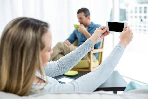 Mujer embarazada sentada en el sofá y usando teléfono inteligente